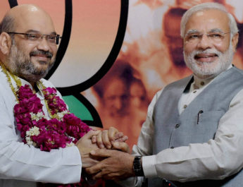 New Delhi: Prime Minister Narendra Modi greets the newly elected BJP President Amit Shah at a press conference at the party headquarters in New Delhi on Wednesday. Home Minister Rajnath Singh is also seen. PTI Photo by Manvender Vashist (PTI7_9_2014_000118B)