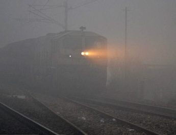 Mirzapur: Train runs through dense fog in Mirzapur on Wednesday. PTI Photo(PTI11_30_2016_000150B)