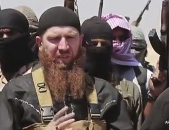 This image made from undated video posted during the weekend of June 28, 2014 on a social media account frequently used for communications by the Islamic State of Iraq and the Levant (ISIL), which has been verified and is consistent with other AP reporting, shows Omar al-Shishani standing next to the group's spokesman among a group of fighters as they declare the elimination of the border between Iraq and Syria. Al-Shishani, one of hundreds of Chechens who have been among the toughest jihadi fighters in Syria, has emerged as the face of the Islamic State of Iraq and the Levant, appearing frequently in its online videos Ñ in contrast to the group's Iraqi leader, Abu Bakr al-Baghdadi, who remains deep in hiding and has hardly ever been photographed. (AP Photo/militant social media account via AP video)