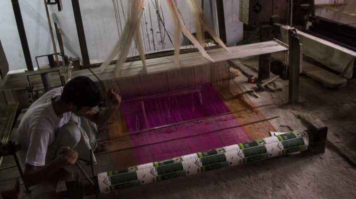 KHOJWAN KIRAIYA, VARANASI, UTTAR PRADESH, INDIA - 2015/07/09: A 22 year old veteran weaver, Abu Umair  works in a handloom factory.  It is one of the promises of India's Prime Minister, the revival of Handloom Industry and better deals to the weavers in Varanasi. Separate policies for Powerloom and Handloom  must be established to avoid cannibalism for both. (Photo by Akshay Gupta/Pacific Press/LightRocket via Getty Images)
